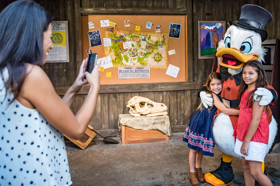 Mom takes picture of kids meeting Scrooge McDuck during Donald's Dino-Bash! at Disney's Animal Kingdom park
