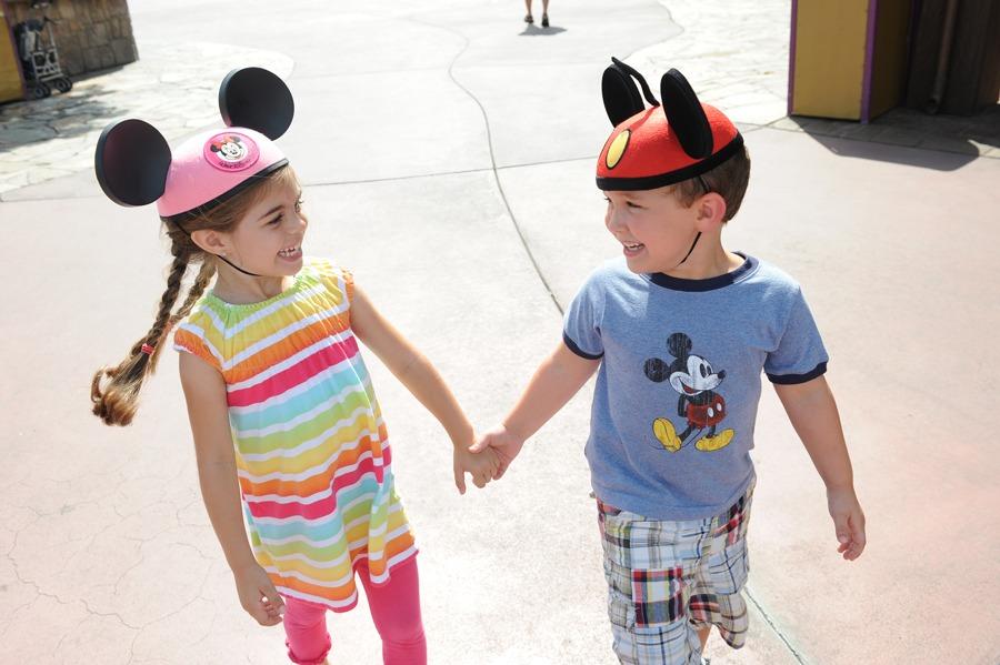 Two kids wearing Mickey ears hold hands