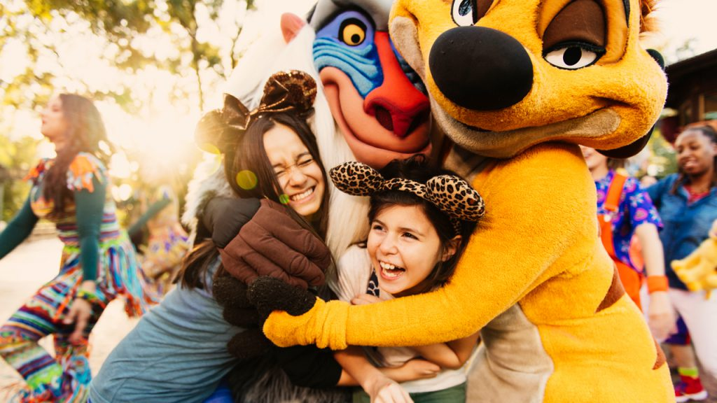Two girls hug Rafiki and Timon at  during the Hakuna Matata Time Dance Party at Disney's Animal Kingdom