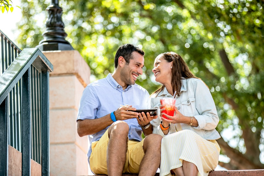 Couple sitting on the steps eating and drinking