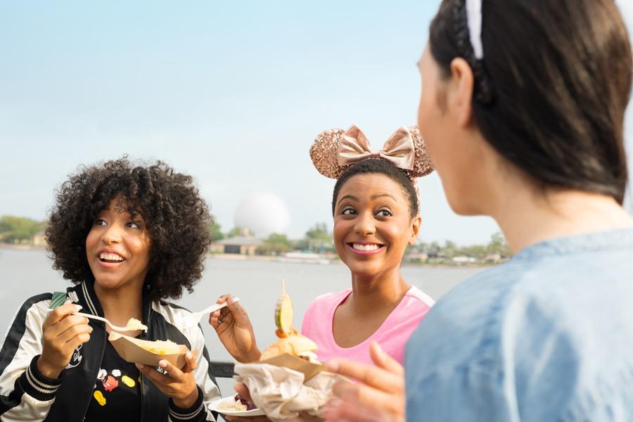 Three friends eating food at the Epcot International Food & Wine Festiva