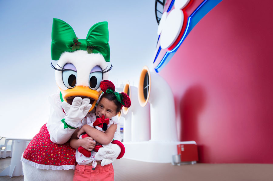 Daisy Duck hugs a young guest aboard Disney Cruise Line