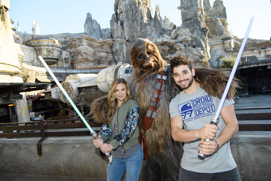 """""""Dancing with the stars"""" contestant """"The Bachelorette"""" Hannah Brown, and her partner, professional dancer Alan Bersten, pose with Chewbacca in Star Wars: Galaxy's Edge"""