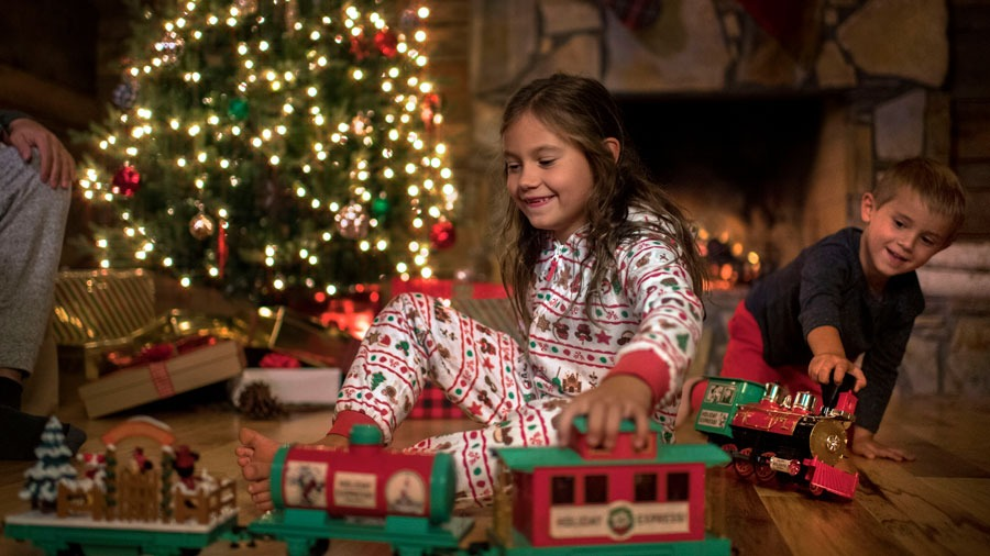 Children wearing holiday merchandise and playing with toy train set