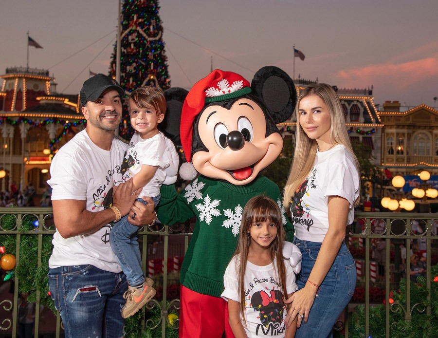 Luis Fonsi, his wife Agueda, daughter Mikaela and son Rocco pose with Mickey Mouse during Mickey's Very Merry Christmas Party at Magic Kingdom Park