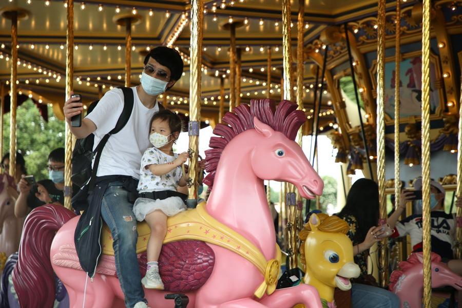 Guests ride Fantasia Carousel at Shanghai Disneyland