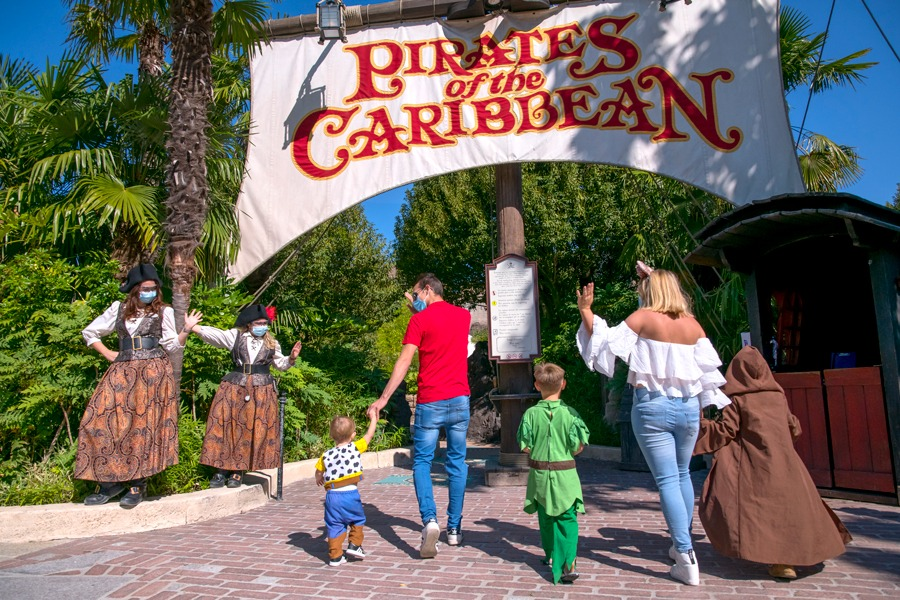 Guests wave to cast members while walking to Pirates of the Caribbean attraction at Disneyland Paris