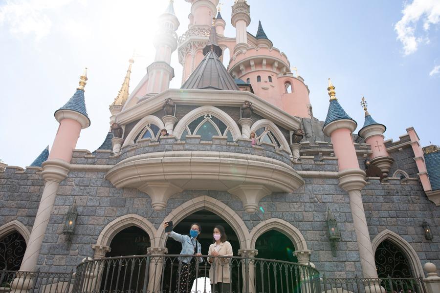 Guests take a selfie at Sleeping Beauty Castle at Disneyland Paris