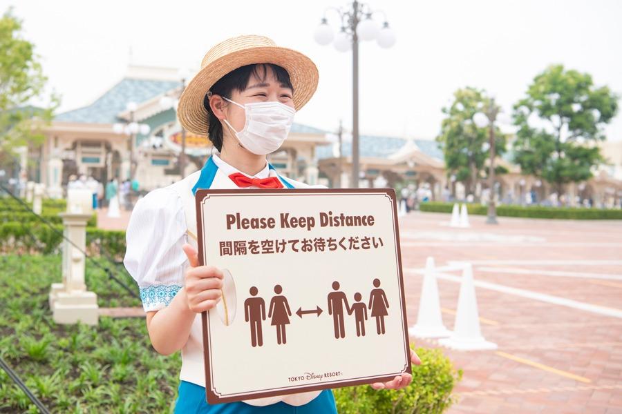 Tokyo Disney Resort cast member holds social distancing sign