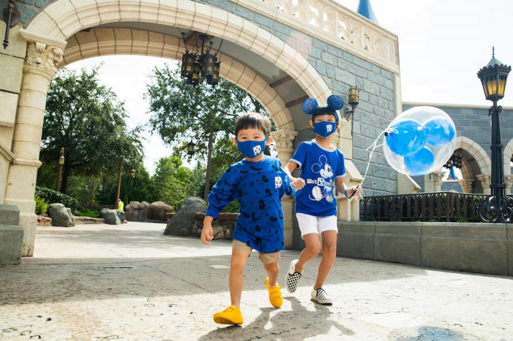 Kids in the new Wishes Come True Blue Mickey Mouse Ear headband, mask, spirit jersey and shirt with Walt Disney World Resort logo