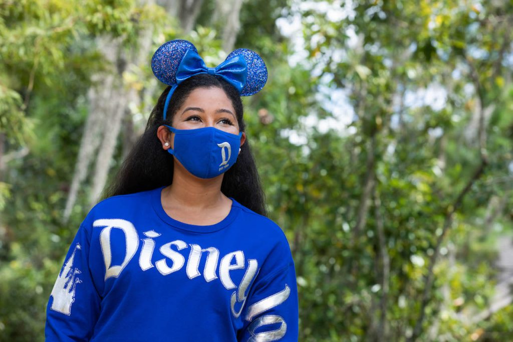 Girl in the new Wishes Come True Blue Minnie Mouse Ear headband, mask and spirit jersey with Disneyland Resort logo