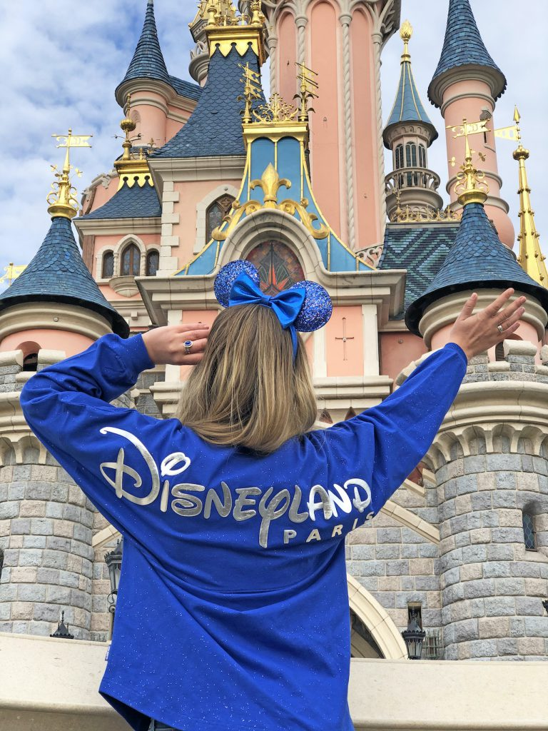 Girl in Wishes Come True Blue Minnie Mouse Ear headband and spirit jersey with Disneyland Paris logo